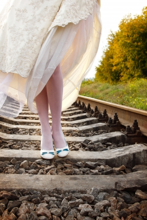 young woman brides walks on the railway, summer nature outdoor, legs closeup photo