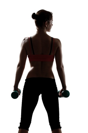 sport young woman with dumbbells, back view, silhouette studio shot over white background photo