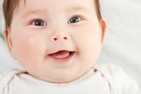 positive feelings: cute funny infant smiling, beautiful kids face closeup with copyspace