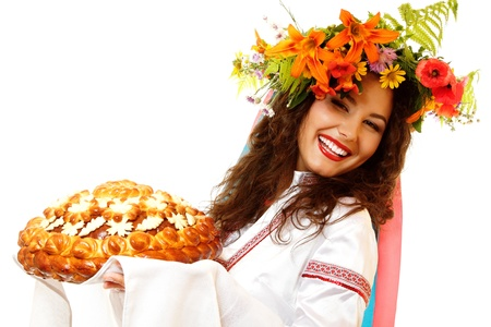 slavic: Beautiful ukrainian young hospitable woman in native costume by tradition holding embroidered towel and round loaf, on white background