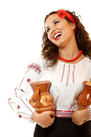 slavic: Beautiful ukrainian young woman in native costume holding earthenware pots and happy smiling over white background
