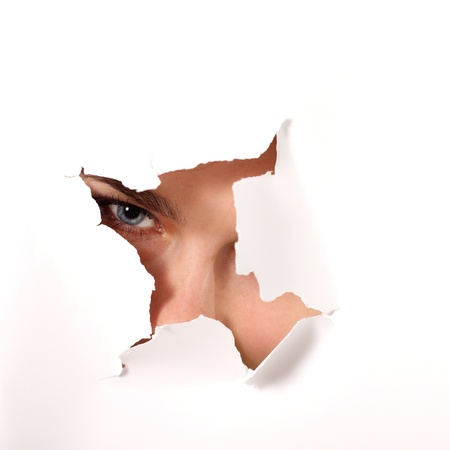 cheerful teen girl peeping surprised through hole of white paper photo