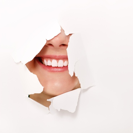 furtively: toothy smile of cheerful teen girl through hole of white paper