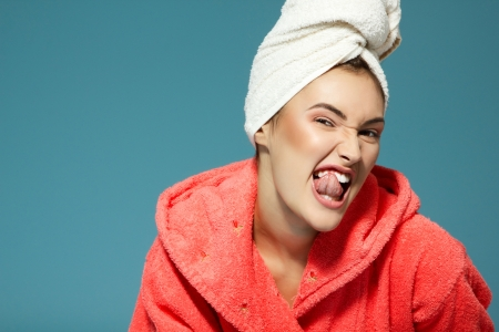 bath gown: Cheerful attractive funny teen girl clean her teeth in the morning. Over blue background