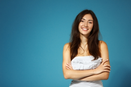 woman smiling: beautiful cheerful teen girl in white top over blue background
