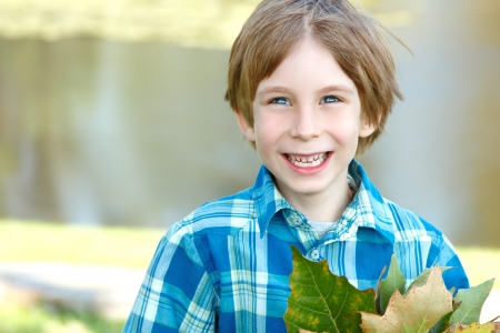 6 years: little happy boy with fall leaves over sunny nature background, portrait of laughing child in park outdoor Stock Photo