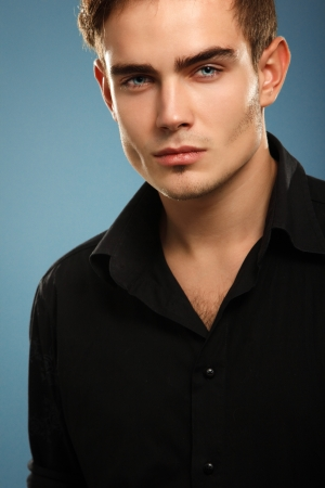 Handsome trendy young man in black shirt, portrait of sexy fashion boy looking right over dark blue background photo