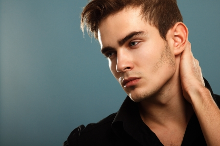 Trendy young man in black shirt, portrait of sexy fashion boy looking right over dark blue photo