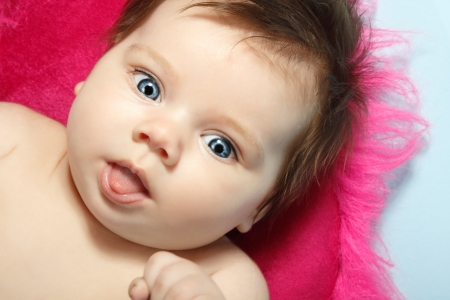 1 2 month: cute funny baby with tongue, beautiful kids face and hands closeup, studio shot