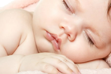 one little boy: cute baby sleeping, beautiful kids face closeup, studio shot