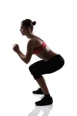 en cuclillas: chica deporte que hace ejercicio en cuclillas, estudio tiro silueta sobre el fondo blanco