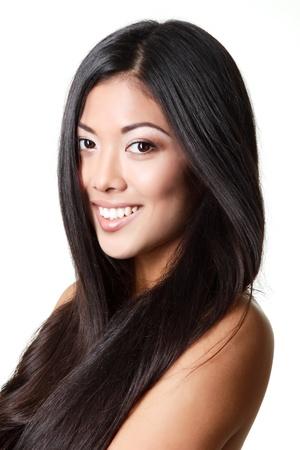 cabello negro: belleza retrato de mujer joven hermosa muchacha sonriente con el pelo largo y negro y la piel limpia sobre blanco Foto de archivo