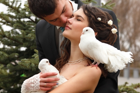 Young attractive wedding couple with pigeons pair, broom kiss bride over park autumn outdoor photo