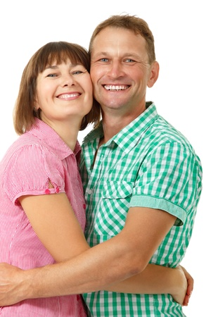 average age: Attractive cheerful woman with man in love smiling over white background. Portrait of happy mature wife hugs her husband Stock Photo