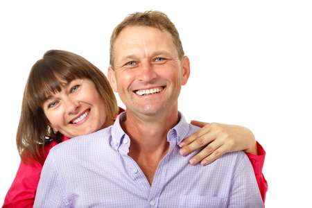 average age: Attractive cheerful woman with man in love smiling over white background. Portrait of happy mature wife hugs her husband, isolated