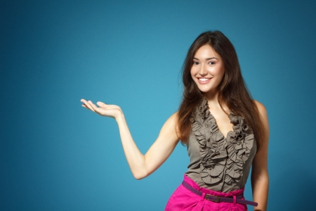 beautiful teen girl showing something with hand, over blue background Stock Photo - 17664543