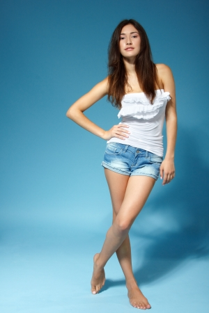 beautiful cheerful teen girl in jean shorts and white top, full length portrait over blue background photo