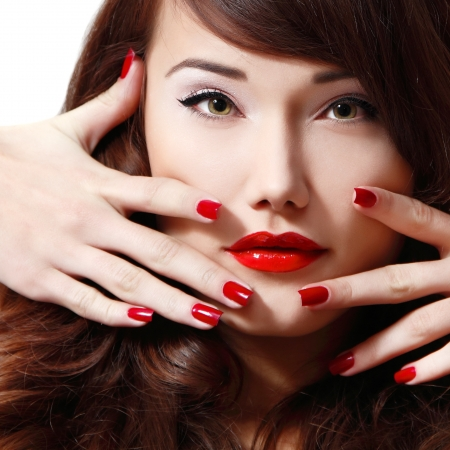 long shot: young woman portrait with long hair, red lipstick and manicure, studio shot