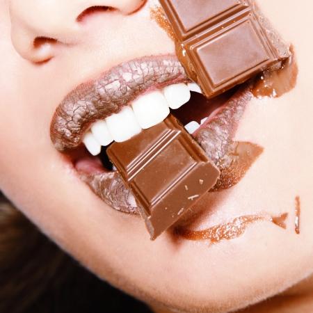 chocolate melt: giovane fresca bella donna di mangiare cioccolato, bellezza femminile dettaglio volto Archivio Fotografico