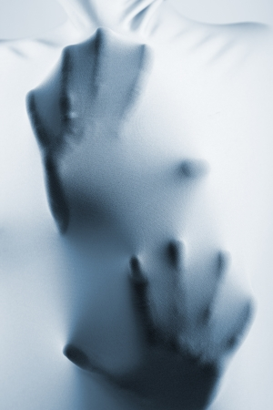 claustrophobia: abstract hands, human arm inside fabric, studio shot toned blue Stock Photo