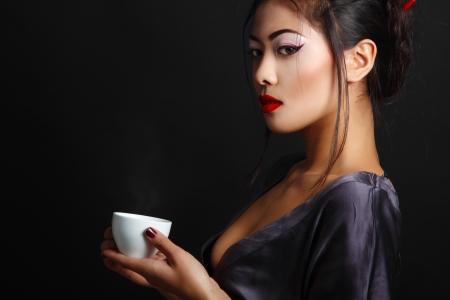 Japanese kimono girl: Người phụ nữ trẻ châu Á xinh đẹp và trà đạo, bắn qua phòng thu backround màu đen với copyspace