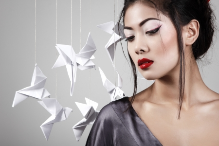 Young beautiful asian woman with origami paper pigeons, studio shot photo