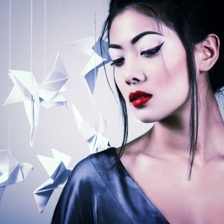geisha: Young beautiful asian woman with origami paper pigeons, studio shot