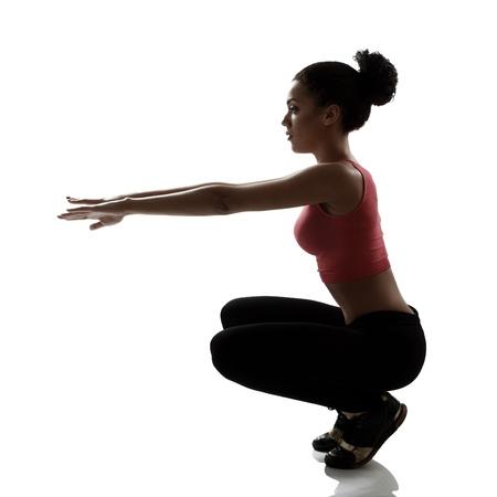 en cuclillas: atleta deporte joven haciendo ejercicio en cuclillas, activo chica fitness silueta disparó sobre fondo blanco