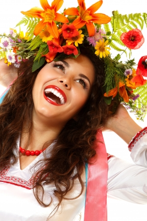 Beautiful ukrainian young woman in garland of summer flowers and native costume dancing on Slavic holiday Ivan-Kupala, on white background photo