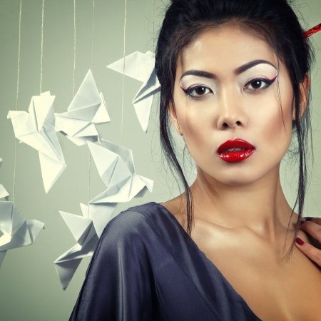 geisha kimono: Young beautiful asian woman with origami paper pigeons, studio shot