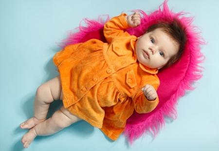 1 2 month: cute infant baby girl in orange dress, beautiful kids full length portrait, studio shot Stock Photo