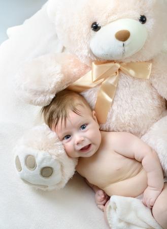 cute funny infant baby boy with big bear, beautiful kids portrait closeup