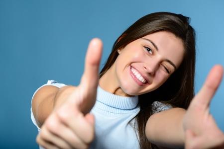 confianza: Retrato de una hermosa chica adolescente confiada y alegre que muestran los pulgares para arriba aislados en azul