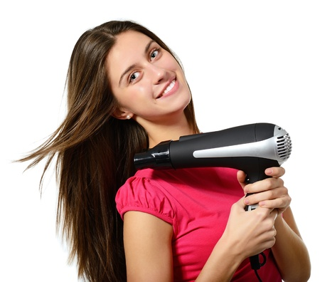 attractive cheerful teenager girl blows dry her hair with hairdryer, over white Stock Photo - 19086251