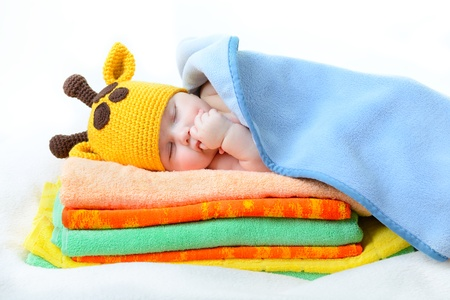 cute sleeping baby boy in funny hand made giraffe hat, beautiful kid dozing on pile of colorful towels with blue plaid, studio shot photo