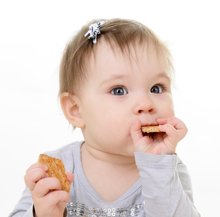over eating: portrait of cute eating little girl toddler, 10 month, studio over white Stock Photo