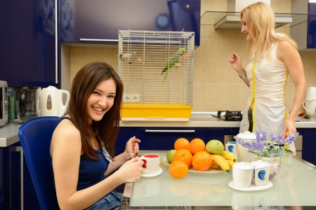 Daughter teenager has breakfast and drinking tea with her mother together in kitchen at home  photo