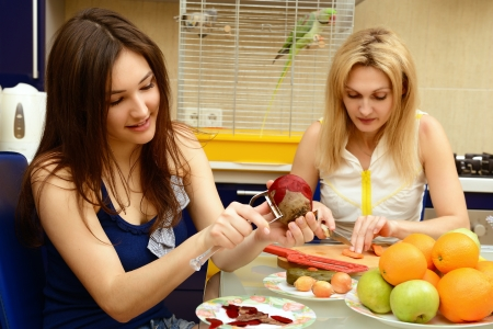 beet: Happy daughter teenager with her mother peel and cut vegetables together in kitchen at home