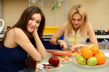 two parrots: Happy daughter teenager with her mother peel and cut vegetables together in kitchen at home