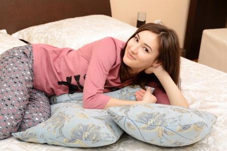 pijama: atractiva chica adolescente alegre en pijama acostado en su dormitorio Foto de archivo