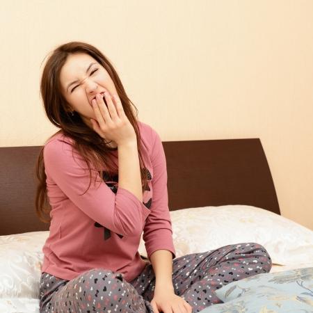 pijama: divertida atractiva chica adolescente alegre en pijama bostezo sentada en la cama en su dormitorio Foto de archivo