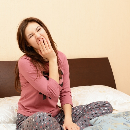 pajamas: funny attractive cheerful teen girl in pajamas yawn sitting on bed in her bedroom Stock Photo