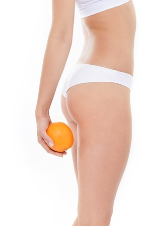 absence: Young woman in underwear with an orange showing absence of cellulite over white background