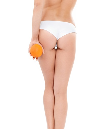 with orange and white body: Young woman in underwear with an orange showing absence of cellulite over white background