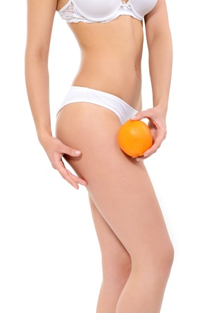 sexy woman panties: Young woman in underwear with an orange showing absence of cellulite over white background