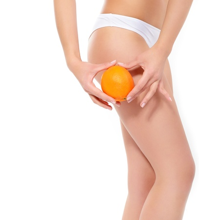 cellulite: Young woman in underwear with orange showing absence of cellulite and perfect body over white background