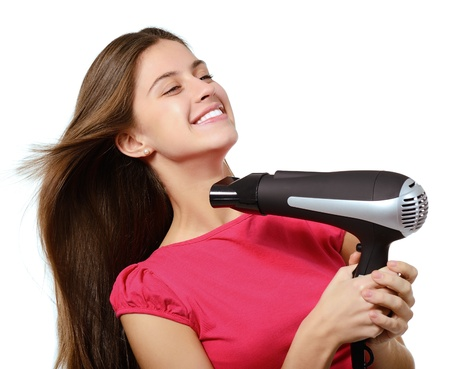 attractive cheerful teenager girl blows dry her hair with hairdryer, over white photo