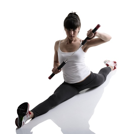 sport karate girl doing splits with nunchaku, fitness woman silhouette studio shot over white background photo