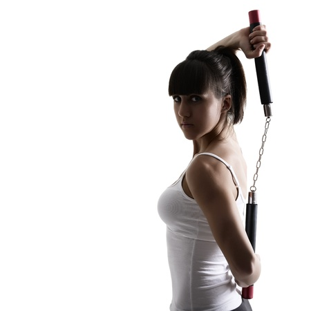 sport karate girl doing exercise with nunchaku, fitness woman silhouette studio shot over white background photo