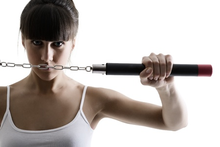 portrait of sport karate girl with nunchaku, fitness woman silhouette studio shot over white background photo